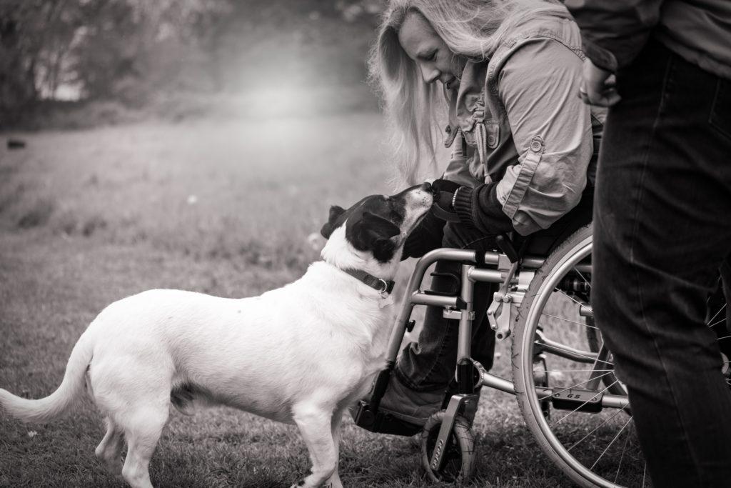 Frau im Rollstuhl streichelt einen Hund