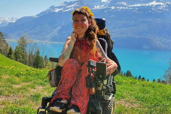 Nadja Schmid, im Rollstuhl sitzend, mit Ausblick auf einen See und Berge im Hintergrund bei schönem Wetter