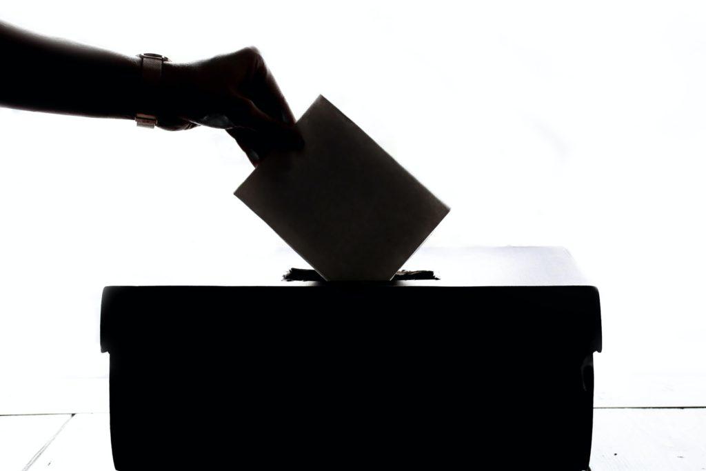 Jemand wirft ein Couvert in die Abstimmungsurne