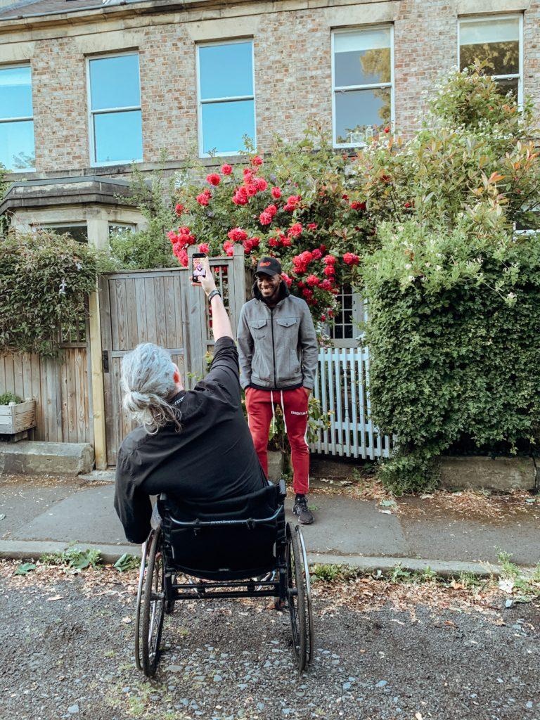 Mann im Rollstuhl macht ein Bild mit seiner Handykamera von seinem Assistenten vor einem Haus mit roten Blumen