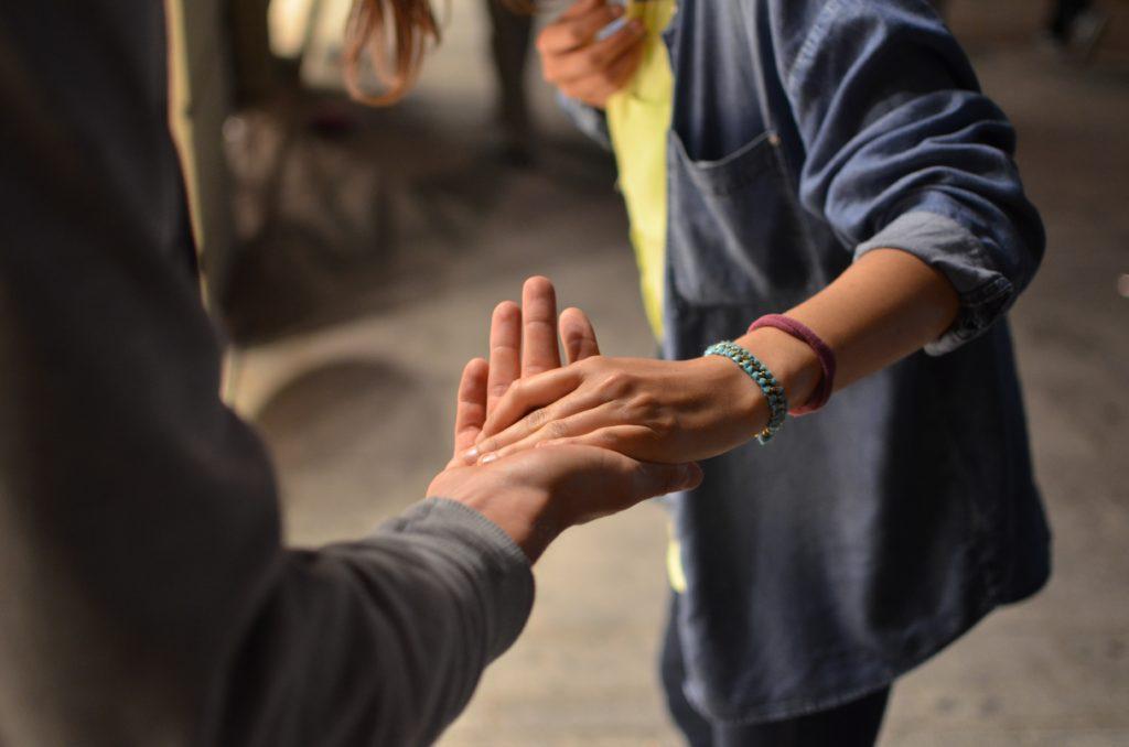 Zwei Menschen nehmen sich bei der Hand