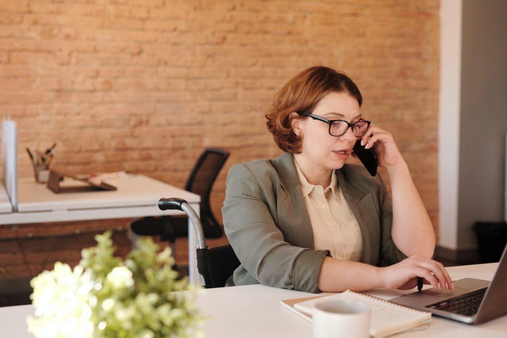 Eine Frau sitzt vor dem Computer und telefoniert