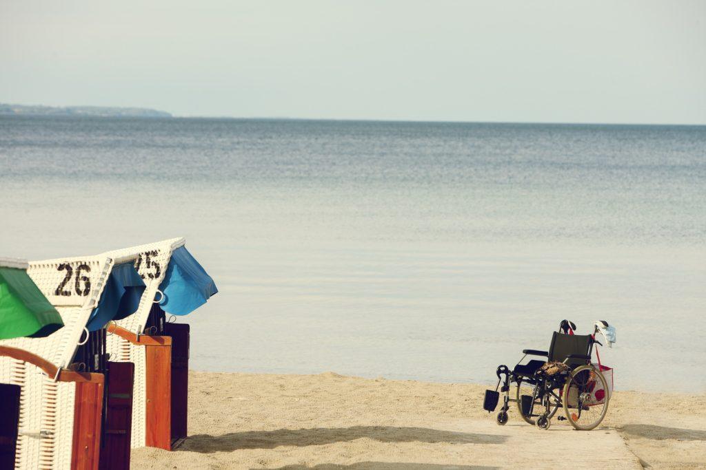 Ein Rollstuhl steht am Ende eines Stegs am Standstrand