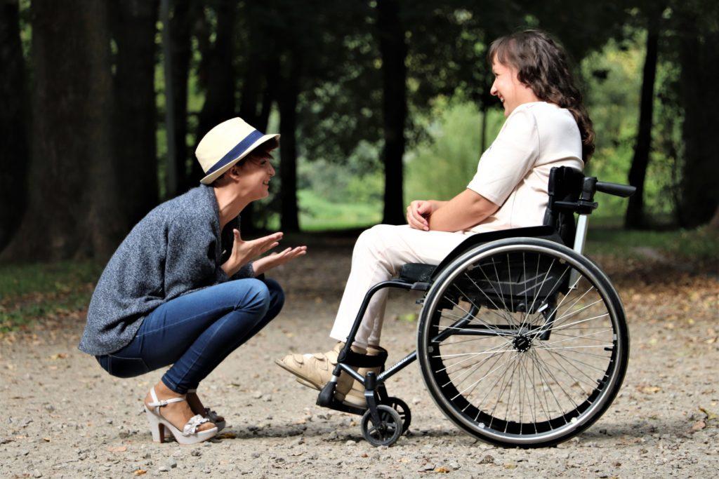 Eine Frau kniet vor einer anderen Frau, die im Rollstuhl sitzt