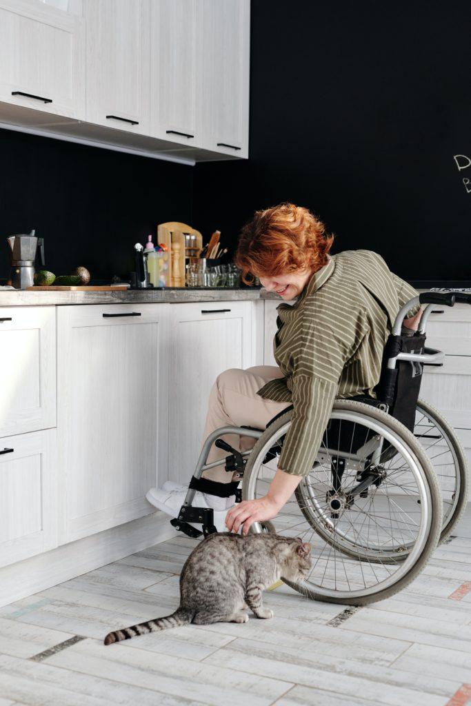 Eine Frau im Rollstuhl in der Küche streichelt eine Katze