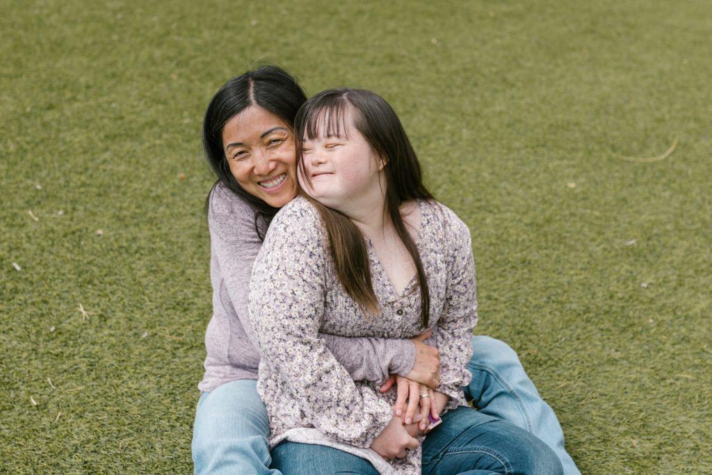 Mutter mit Tochter sitzen auf einer grünen Wiese