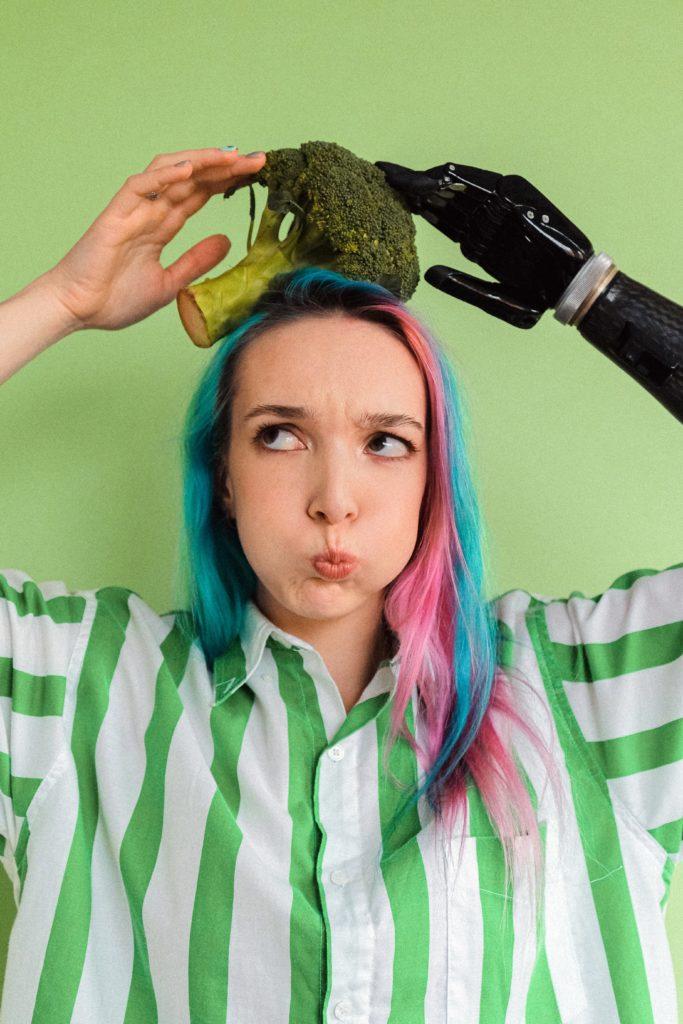 Eine junge Frau mit farbigen Haaren und einer Armprothese hält sich einen Brokkoli auf dem Kopf.