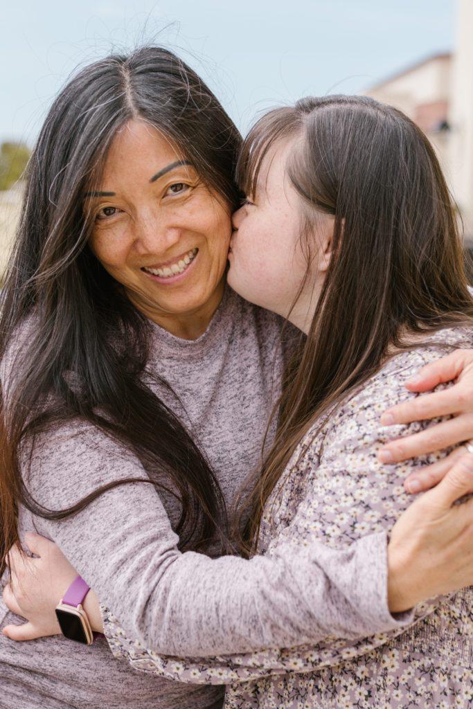 Ein junges Mädchen küsst seine Mutter auf die Wange